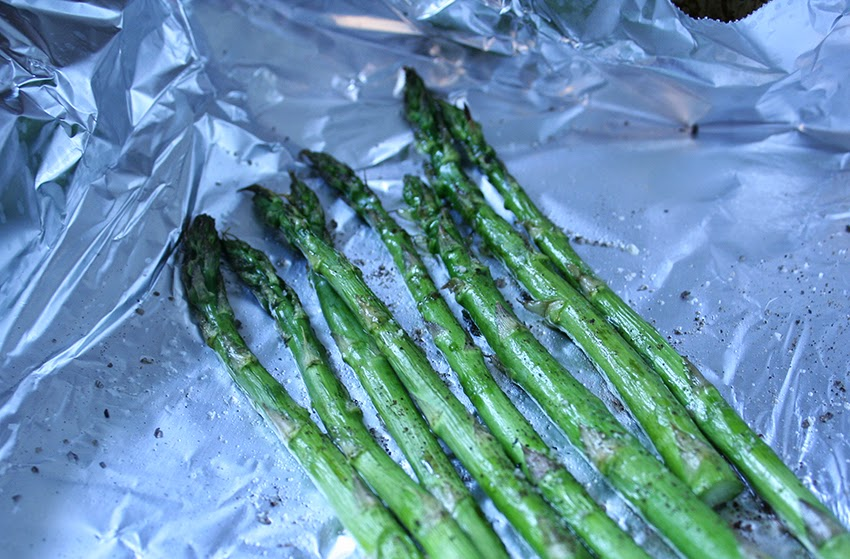Asparagus is seasoned and broiled.